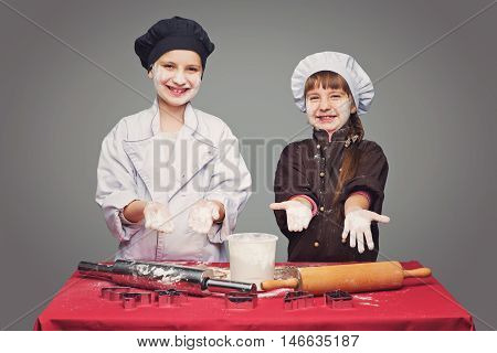 Beautiful boy and girl in chef clothes making christmas cookies with plunger over grey background. Copy space.