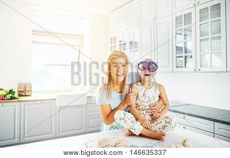 Bright kitchen scene with copy space of woman holding laughing child in silly purple eyeglasses while seated on table