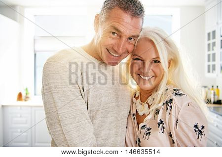 Joyful middle aged man and woman standing close together with heads touching in bright kitchen