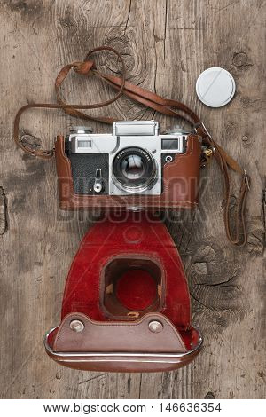 Retro camera in leather case on wooden background top view