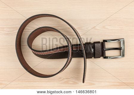 Brown leather belt with buckle lying on a wooden surface with space for your text
