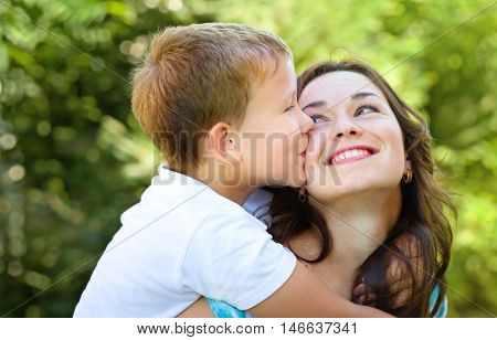 Son is kissing his happy mother, outdoor shoot