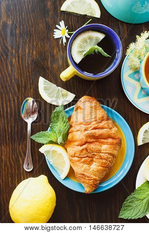 Tea Set: Green Tea With Lemon And Mint, Croissant With A Crispy Crust, Wooden Background