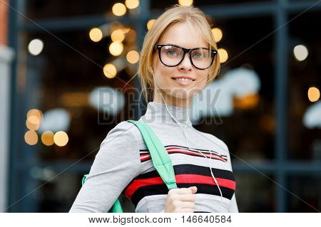 Student in glasses, with headphones on background of glass showcases