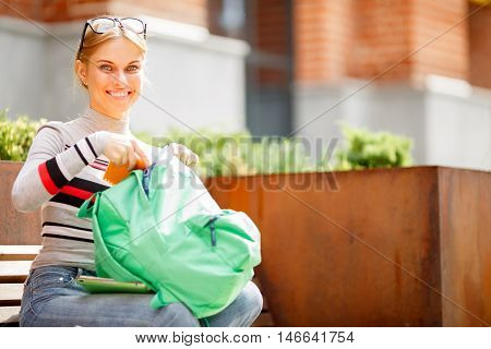 smiling girl adds Notebook Backpack sitting on bench