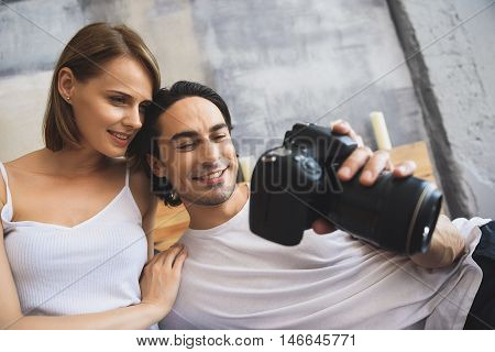 Young smiling photographer holding camera while his girlfriend watching pictures on his camera