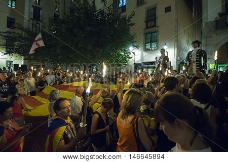 BARCELONA SPAIN - SEPTEMBER 10 2016: People takes the large flag of the Catalonia region to the streets during the night eve of La Diada the Catalan National Day at Barcelona on September 10 2016.