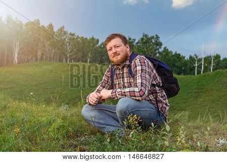 Man sits on a hill and watching the sunset. Tourist with backpack on green grass. Sun going down. A guy with a beard in a plaid shirt meets the sunset in nature.