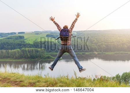 A man with a backpack jumping up on a hill. The guy in a checkered shirt put his hands up to the sky. Freedom and unity with nature. Sun going down. Tourist outdoors enjoying the scenery.