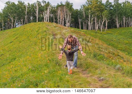 Son runs to meet the father. Family holiday in nature the boy runs across the grass on a hill in the forest.