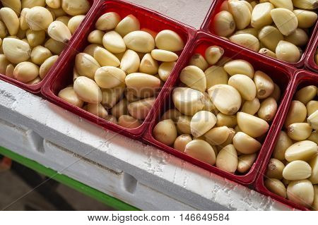 Peeled garlic cloves in boxes at the market