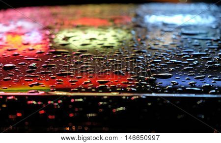 Raindrops and reflected illumination by car in the evening