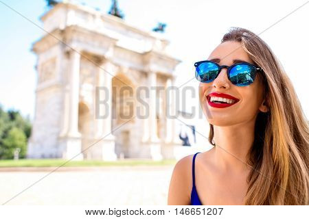 Young smiling woman in front of the triumphal arch in Milan. Having a great vacations in Milan city