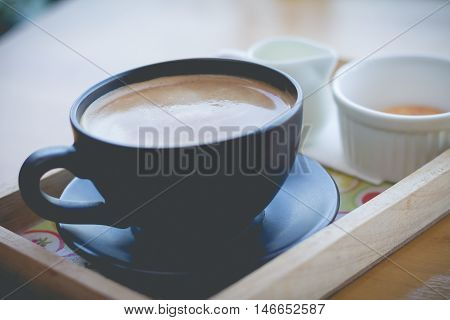 Black cup of coffee. Hot coffee in afternoon break. coffee mocha on the wood desk.(selective focus vintage effect)
