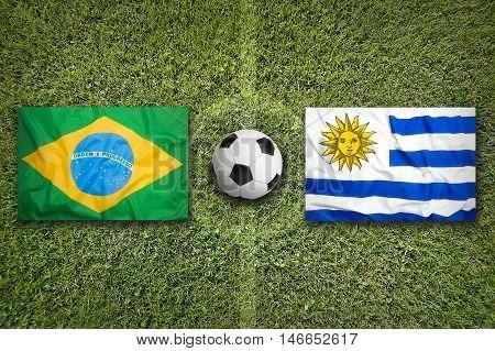 Brazil Vs. Uruguay Flags On Soccer Field, 3D Illustration