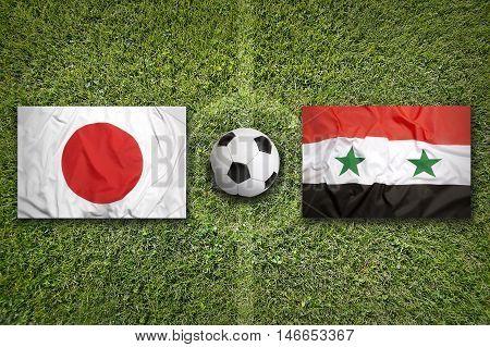 Japan vs. Iraq flags on green soccer field, 3D illustration