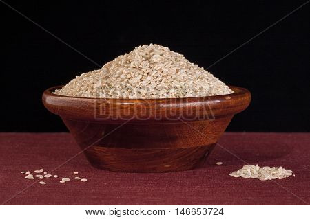 Bowl of raw brown rice. A wooden bowl filled with uncooked raw brown rice.