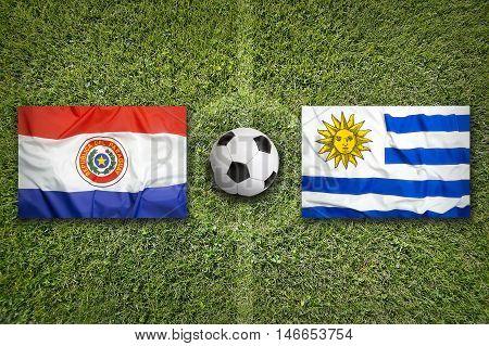 Paraguay Vs. Uruguay Flags On Soccer Field, 3D Illustration