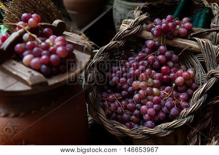 still life of grapes and rustic wicker baskets air