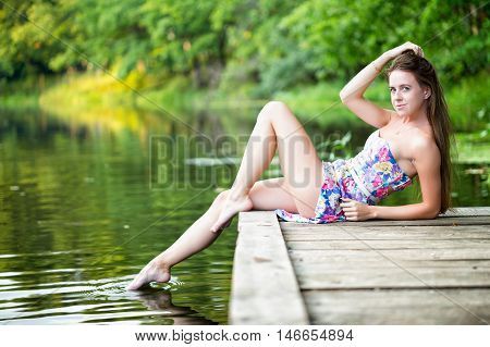 Woman relaxes by lake sitting on edge of a wooden jetty .Sunny joyful summer day or evening concept.