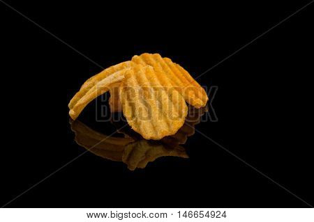 Potato chip on black surface closeup reflection detail