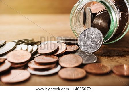 Save money concept, Coins spilling out of a glass bottle, Money for income and expenditure selective focus, Save money for prepare in the future
