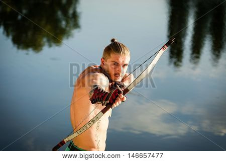 Male Archer on the banks of the river pulls the arrow