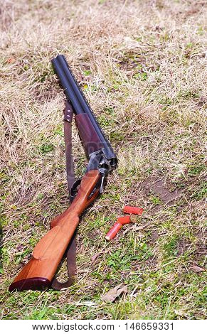 A view of a double barrel shotgun lying on the ground with several red shotgun shells nearby. The shotgun is open ready to be loaded.