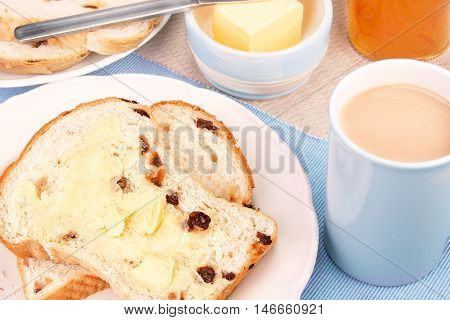 Sliced fruit loaf with sultanas and a cup of tea with milk. Selective focus