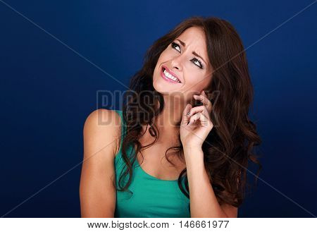 Concentrated beautiful woman thinking and looking up on empty space background. Curly brown long hair style.