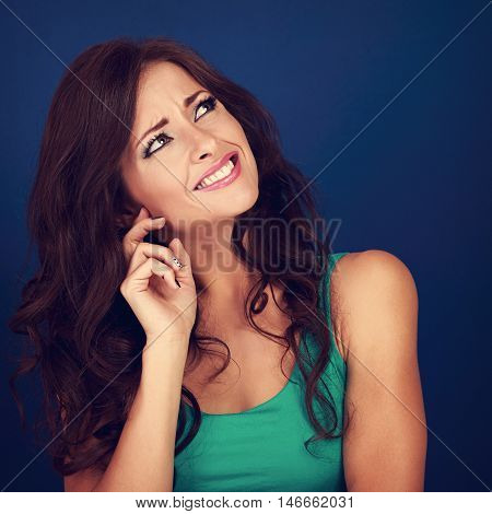 Concentrated Beautiful Woman Thinking And Looking Up On Empty Blue Space Background. Curly Brown Lon