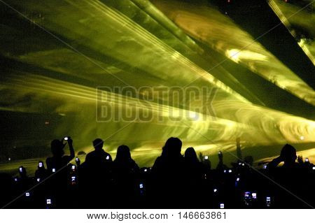Silhouetted crowd attending laser show. Streaks of light projected overhead.