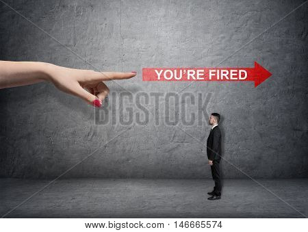 Big female arm pointing at red arrow with 'you're fired words' over small businessman. Boss and subordinate. Unemployment. Losing a job.