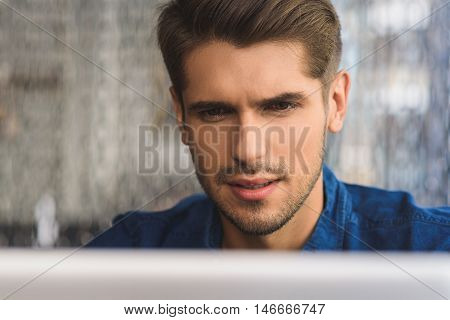 closeup of a man looking at laptop with thoughtful face