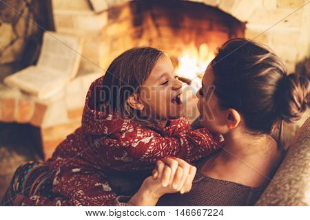Mom with child playing and chilling by the fire place some cold evening, winter weekends, cozy scene