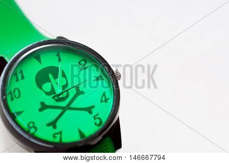 Selective focus on green color watch dial with danger symbol. Skull and bones as time the killer idea.
