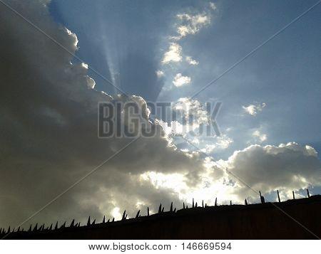 Céu com nuvens e por trás o brilho do sol.