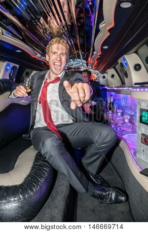 Excited Man Holding Champagne Flute While Gesturing In Limo