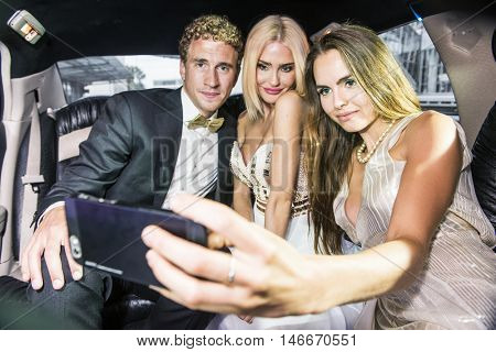 Three smartly dressed people, ready for an event, taking a selfie with a mobile phone in the back or a luxurious limousine