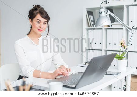 Close-up portrait of a businesswoman at her workplace working with pc, looking in camera, wearing office suit