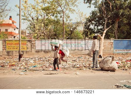 JAIPUR, INDIA - JAN 21, 2015: Unidentified poor children collect rubbish on the streets for recycling on January 21, 2015 in Rajasthan. Jaipur with population 6664000 people is a capital of Rajasthan