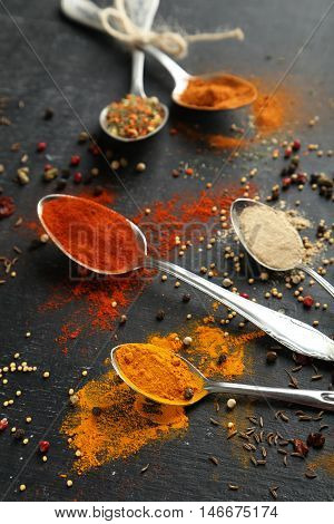 Spoons With Spices On Black Wooden Table