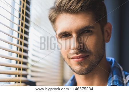 pensive good looking bearded face of a man in front of  jalousie