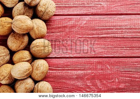 Walnuts on a red wooden table, close up