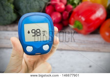 Hand holding meter. Diabetes doing glucose level test. Vegetables in background