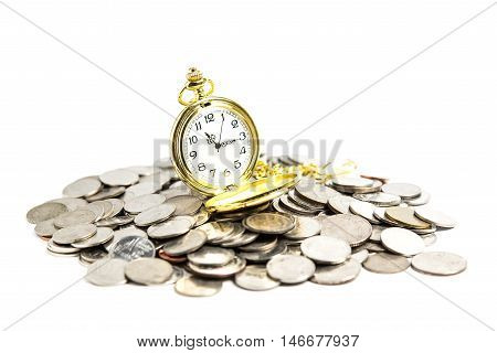 Vintage pocket watch on pile of coins. Time and money concept.