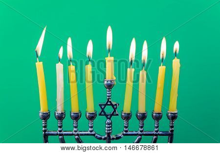 Hanukkah menorah with candles Hanukkah candles happy burning green background isolation