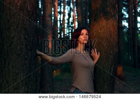 Portrait of a girl at sunset in mysterious forest