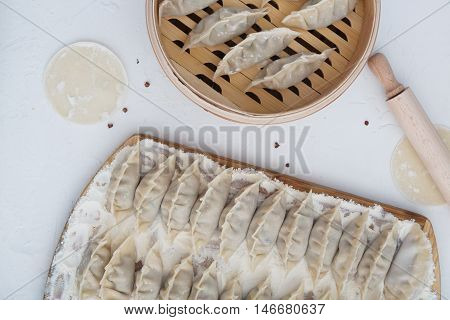 raw dumpling on bamboo wickerwork with flour and pepper.