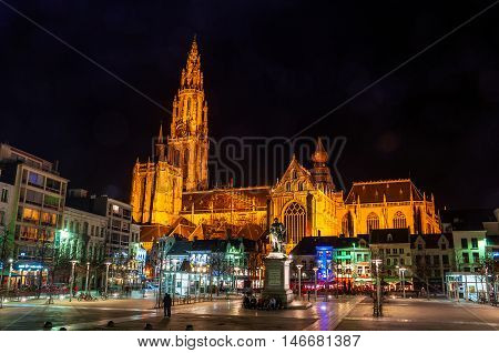 Roman Catholic cathedral in Antwerp Belgium at night different bars cafes and restaurants at the square. Nightlife in european city